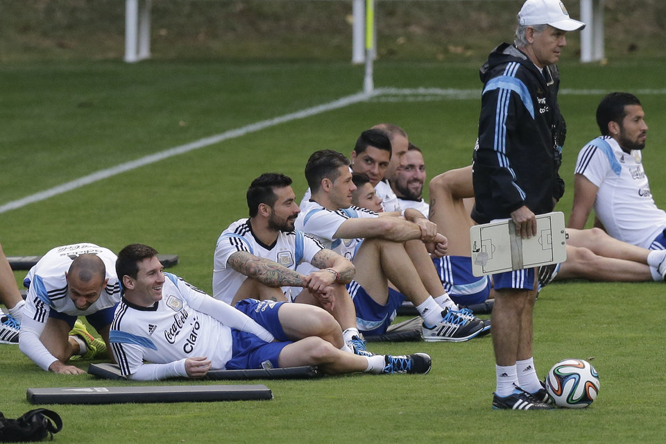 Photo - Argentina's Javier Mascherano, left, and Lionel Messi, second left, sit with teammates next to Argentina's head coach Alejandro Sabella, right, during a training session in Vespesiano, near Belo Horizonte, Brazil, Thursday, July 10, 2014. On Sunday, Argentina faces Germany for the World Cup final soccer match in Rio de Janeiro. (AP Photo/Victor R. Caivano)