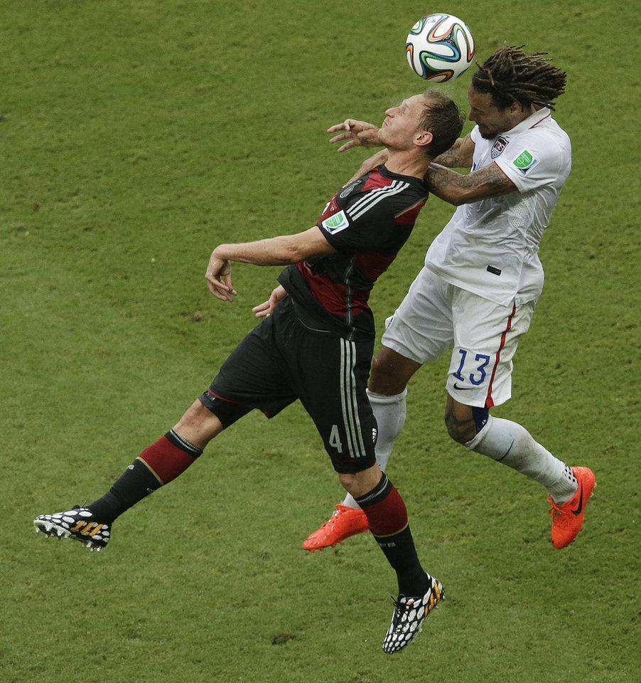 Photo - Germany's Benedikt Hoewedes and United States' Jermaine Jones go for a header during the group G World Cup soccer match between the USA and Germany at the Arena Pernambuco in Recife, Brazil, Thursday, June 26, 2014. (AP Photo/Hassan Ammar)
