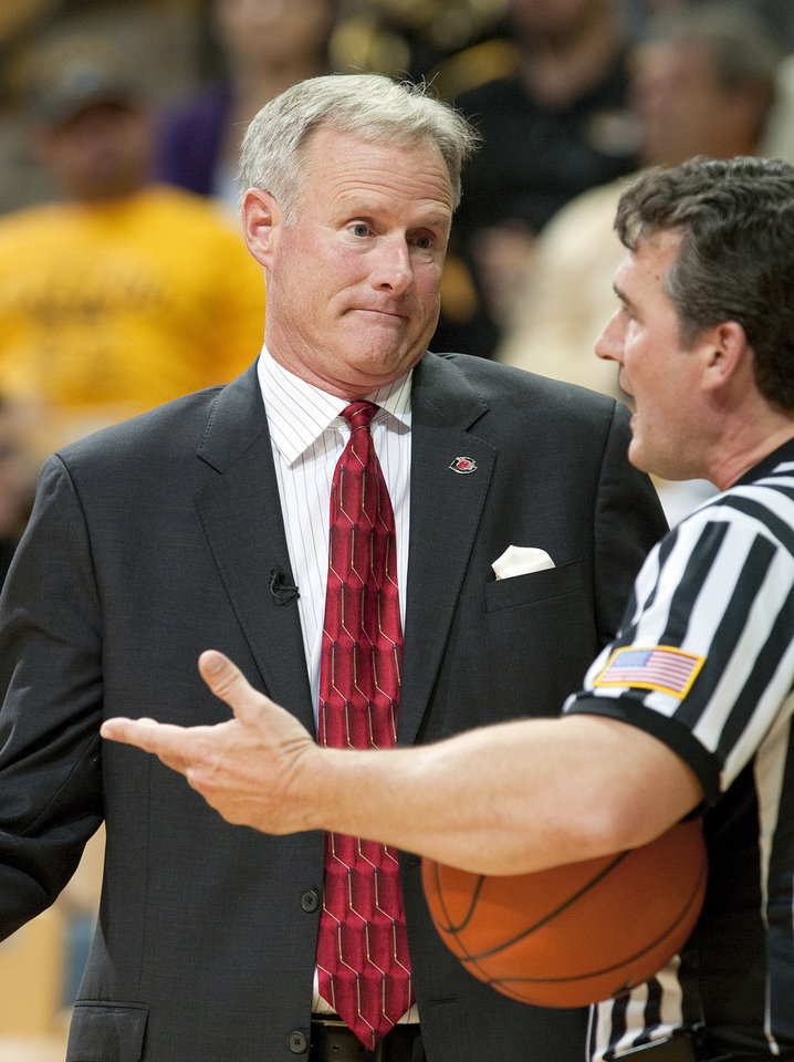 Photo - FILE - In this Nov. 1, 2013, file photo, Central Missouri head coach Kim Anderson, left, argues a call with the referee during the second half of an NCAA college basketball exhibition game against Missouri in Columbia, Mo. Missouri announced Monday, April 28, 2014, that it has hired Anderson, a former star player and longtime aide to Norm Stewart, as its men's basketball coach. (AP Photo/L.G. Patterson, File)