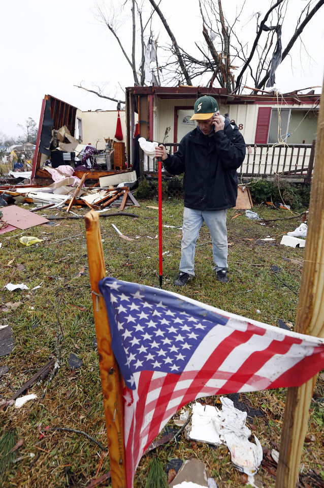 Photo - Brian Bernard of Petal, Miss., walks behind a makeshift memorial in front of his tornado damaged home Tuesday, Feb. 12, 2013. The home was one of several destroyed by Sunday's tornado touchdown. following the  Sunday afternoon tornado that caused damage throughout several communities in mid-state. (AP Photo/Rogelio V. Solis)