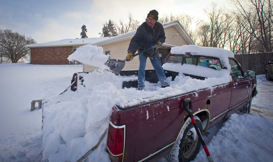 Josh Buschbom shovels out his truck bed in Des Moines Friday, Feb. 22, 2013, after an overnight snowstorm dumped six inches of snow in Des Moines.  The snowstorm left behind varying amounts of snow and ice across the Midwest, causing difficult travel conditions. Powerful wind gusts created large snow drifts on many roadways, making navigating the slick conditions a challenge.   (AP Photo/The Des Moines Register, Rodney White)