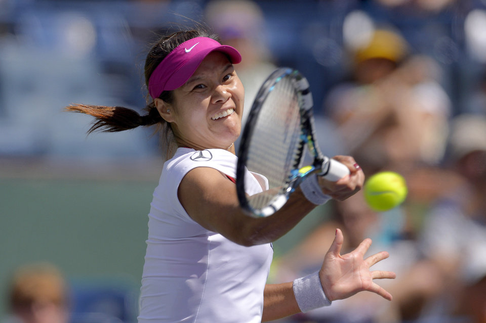 Photo - Li Na, of China, hits to Dominika Cibulkova, of Slovakia, during a quarterfinal match at the BNP Paribas Open tennis tournament, Thursday, March 13, 2014 in Indian Wells, Calif. (AP Photo/Mark J. Terrill)