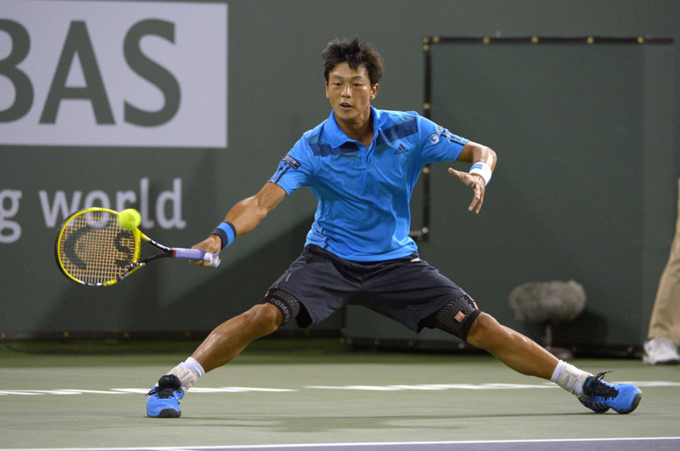 Photo - Lu Yen-Hsun, of Taiwan, returns a shot to John Isner, of the United States, at the BNP Paribas Open tennis tournament, Tuesday, March 11, 2014, in Indian Wells, Calif. (AP Photo/Mark J. Terrill)