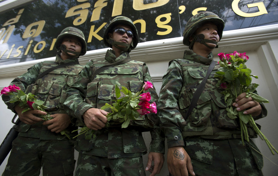 Photo - Thai soldiers hold roses they received from military supporters in Bangkok, Thailand Tuesday, May 27, 2014.  Last Thursday's military takeover, Thailand's second in eight years, deposed an elected government that had insisted for months that the nation's fragile democracy was under attack from protesters, the courts, and finally the army.    (AP Photo/Sakchai Lalit)