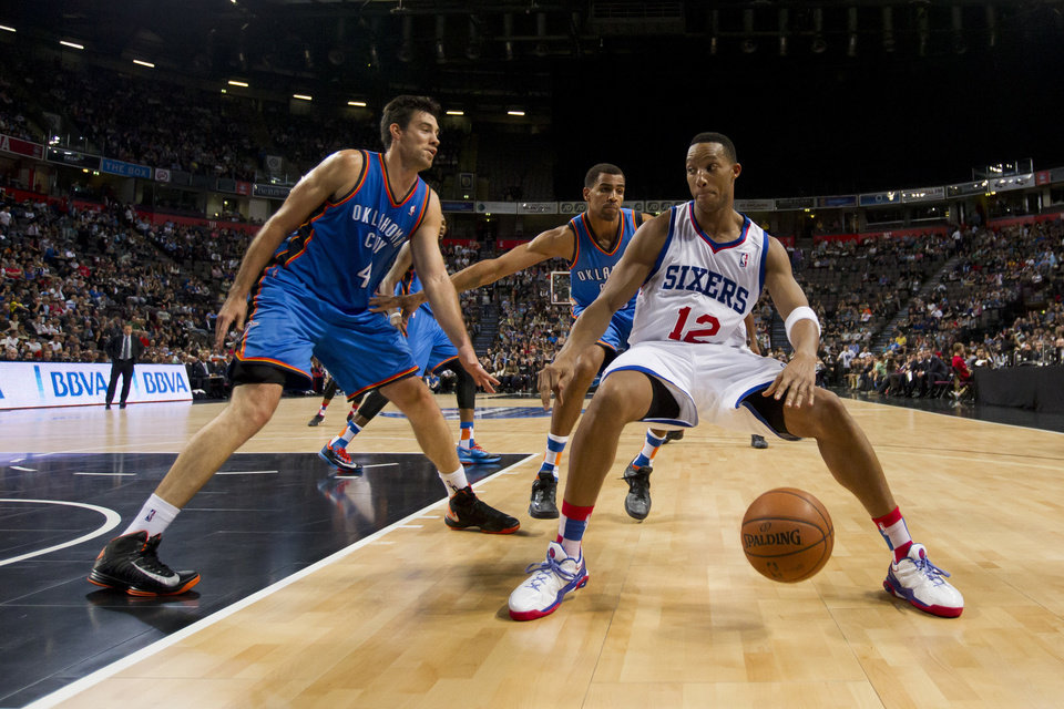 Philadelphia 76ers' Evan Turner, right, keeps the ball from Oklahoma City Thunder's Nick Collison, left, as Thabo Sefolosha looks on during their NBA preseason basketball game at the Phones4 u Arena in Manchester, England, Tuesday, Oct. 8, 2013. (AP Photo/Jon Super) ORG XMIT: MJS105