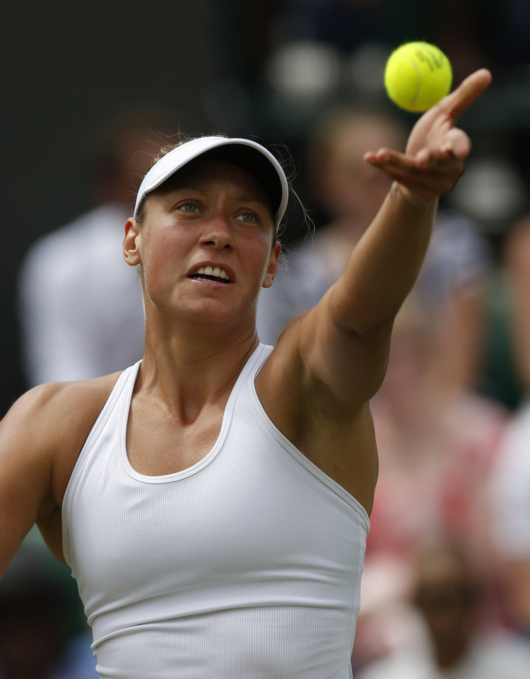 Photo - Belgium's Yanina Wickmayer serves to Australia's Samantha Stosur during their first round match at the All England Lawn Tennis Championships in Wimbledon, London,  Monday, June  23, 2014. (AP Photo/Sang Tan)