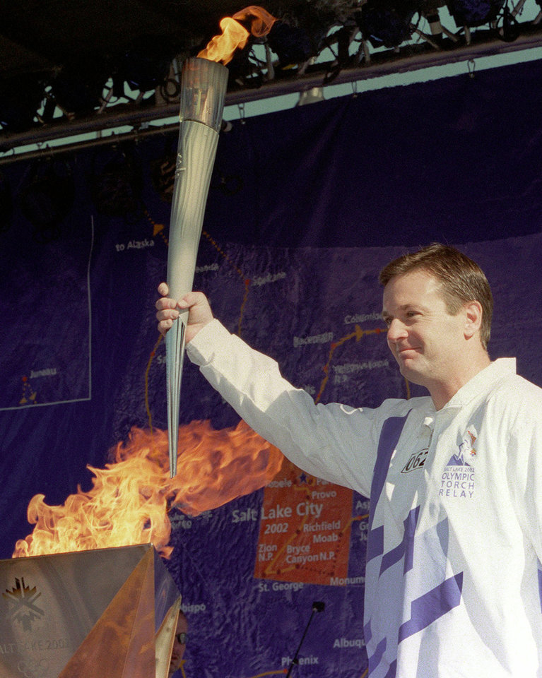 Photo - OLYMPIC TORCH RUN, OU: Oklahoma college football coach Bob Stoops stands before the crowd after lighting the Olympic cauldron Friday, Jan. 11, 2002, in Oklahoma City. After a brief presentation, the Olympic flame was carried throughout the city led by former Olympic gymnasts Nadia Comaneci and Bart Conner, who own a gym in Norman, Okla. (AP Photo/Andrew Laker)