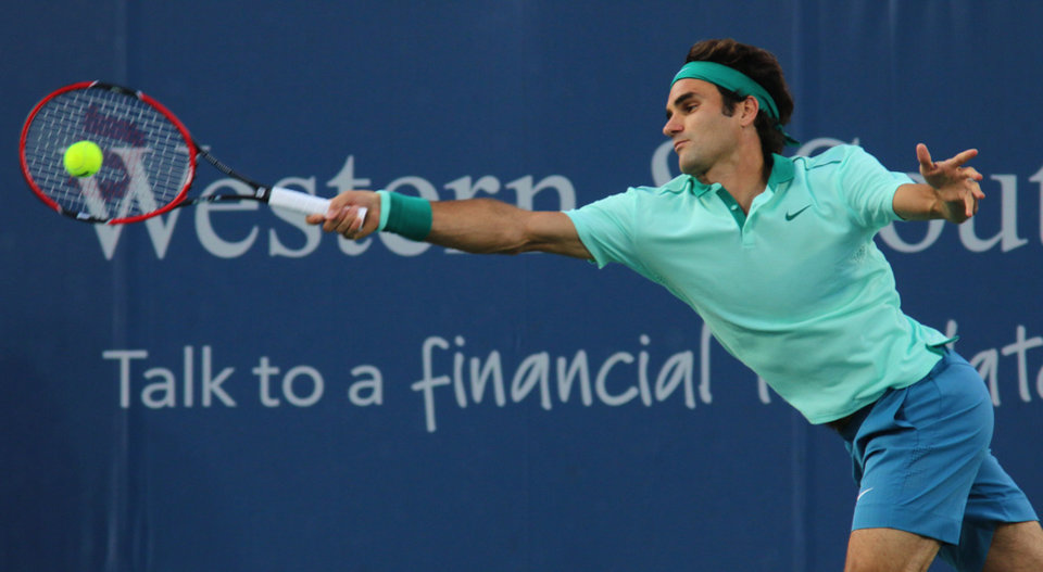 Photo - Roger Federer, of Switzerland, returns a serve to Andy Murray, of Britain, at the Western & Southern Open tennis tournament, Friday Aug. 15, 2014, in Mason, Ohio. (AP Photo/Tom Uhlman)