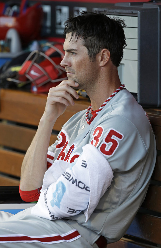 Photo - Philadelphia Phillies starting pitcher Cole Hamels rests in the dugout in the fourth inning of a baseball game against the Cincinnati Reds, Friday, June 6, 2014, in Cincinnati. (AP Photo/Al Behrman)