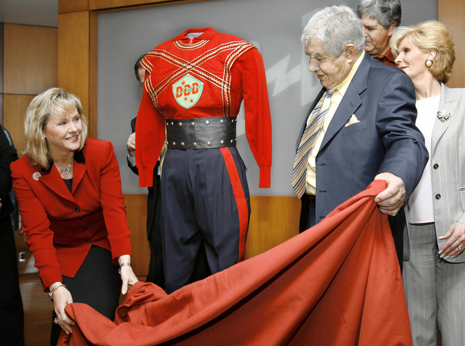 OKLAHOMA HISTORY CENTER DONATION: Lt. Gov. Mary Fallin, left, helps radio and television pioneer Danny Williams remove the covering from an original costume worn by Williams when he played the role of 3-D Danny on WKY-TV. At far right is his wife, Maureen Staff photo by Jim Beckel.