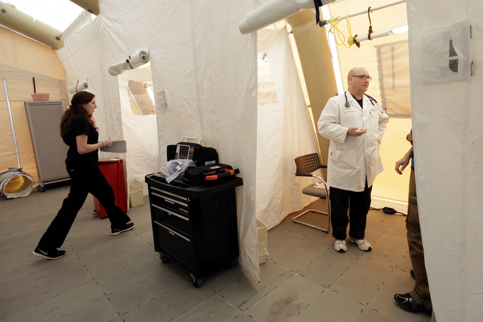 Photo - Registered nurse Michelle Newbury, left, and physician assistant Scott Fillman meet with patients, not pictured, in a tent set up for a people with flu symptoms, just outside the emergency entrance at the Lehigh Valley Hospital Thursday, Jan. 10, 2013, in Allentown, Pa.  The Pennsylvania Department of Health designated flu as now