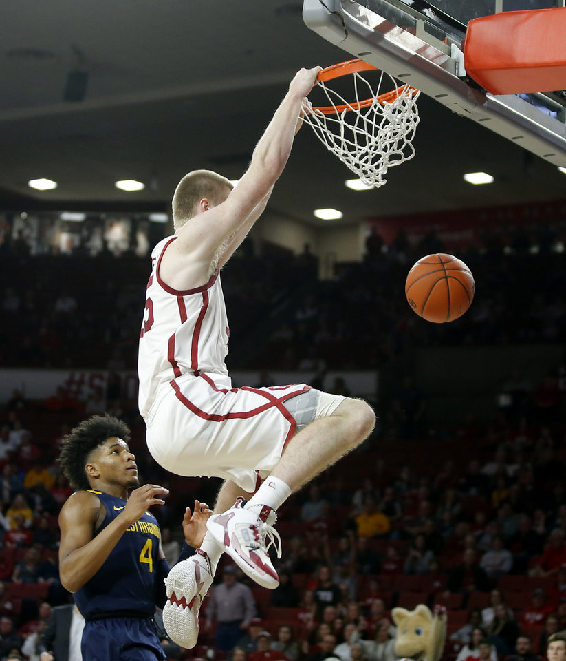 Photo - Oklahoma's Brady Manek (35) dunks over West Virginia's Miles McBride (4) during an NCAA mens college basketball game between the University of Oklahoma Sooners (OU) and the West Virginia Mountaineers at the Lloyd Noble Center in Norman, Okla.,Saturday, Feb. 8, 2020. Oklahoma won 69-59. [Bryan Terry/The Oklahoman]