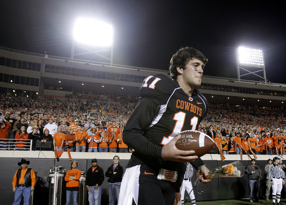 Photo - OSU's Zac Robinson (11) runs on the field as Robinson is recognized for senior night at the college football game between Oklahoma State University (OSU) and the University of Colorado (CU) at Boone Pickens Stadium in Stillwater, Okla., Thursday, Nov. 19, 2009. Photo by Sarah Phipps, The Oklahoman