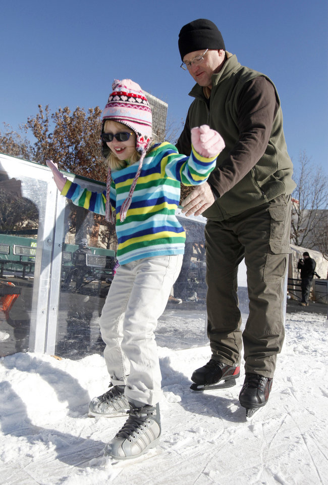 Left: John Hubert helps his  daughter, Isabel, 7, learn to skate Saturday at the Devon Ice Rink.