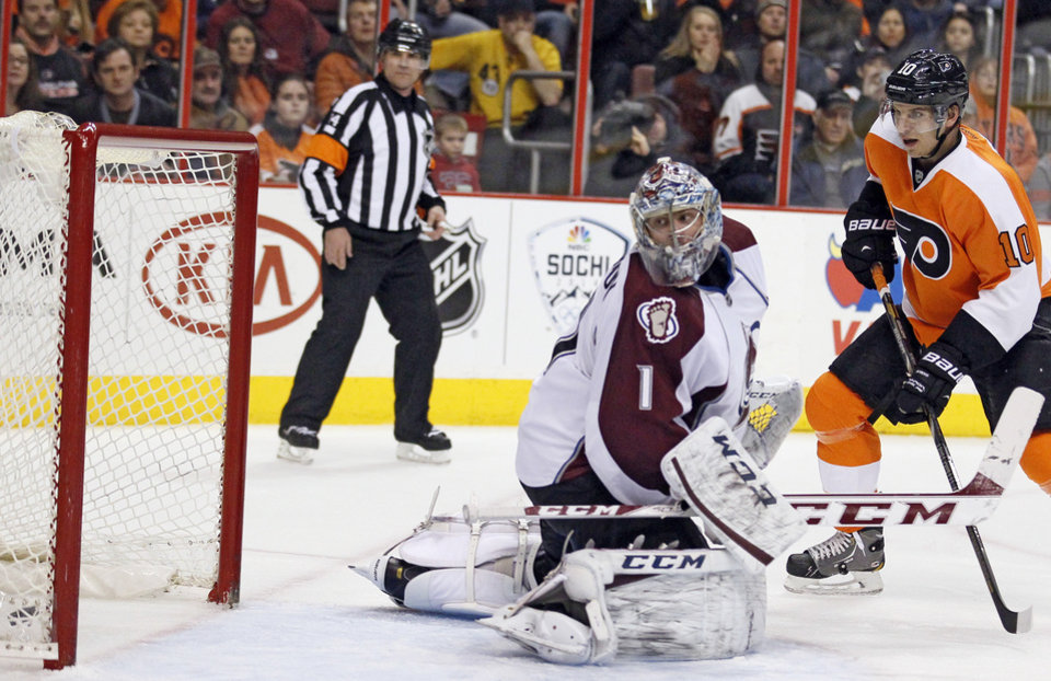 Photo - Colorado Avalanche goalie Semyon Varlamov looks back at the puck in the net, lower left, shot by Philadelphia Flyers' Mark Streit, not pictured, as Brayden Schenn, right, looks on during the second period of an NHL hockey game, Thursday, Feb. 6, 2014, in Philadelphia. (AP Photo/Tom Mihalek)