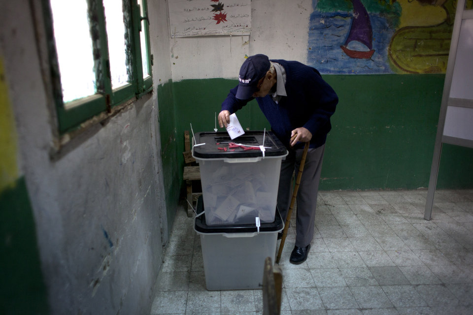 An Egyptian man casts his vote in a ballot box at a polling station in a referendum on a disputed constitution drafted by Islamist supporters of President Mohammed Morsi in Cairo, Egypt, Saturday, Dec. 15, 2012. Egyptians were voting on Saturday on a proposed constitution that has polarized their nation, with Morsi and his Islamist supporters backing the charter, while liberals, moderate Muslims and Christians oppose it. (AP Photo/Nasser Nasser)