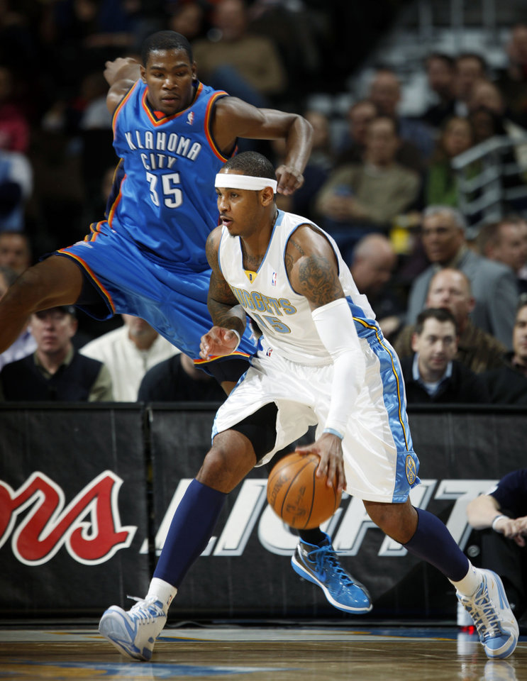 Photo - Denver Nuggets forward Carmelo Anthony, front, slips past Oklahoma City Thunder forward Kevin Durant  in the first quarter of an NBA basketball game in Denver on Monday, Dec. 14, 2009. (AP Photo/David Zalubowski) ORG XMIT: CODZ104