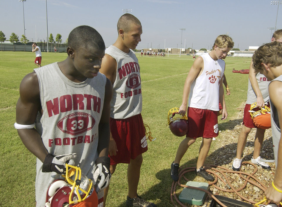 Photo - Oklahoma City, OK. 8/10/04    Putnam North players Deji Karim and Sam Bradford take a break during the first day of high school football practice. Staff photo by Paul Hellstern.