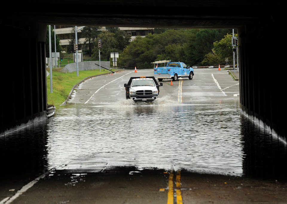 Photo - A traffic control vehicle transits a flooded underpass in San Rafael, Calif., on Sunday, Dec. 2, 2012. Days of heavy rains have left the region saturated and several rivers are expected to flood their banks Sunday afternoon. (AP Photo/Noah Berger)