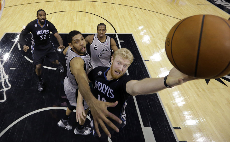 Photo - Minnesota Timberwolves' Chase Budinger, right, drives past San Antonio Spurs' Tim Duncan, center, to score during the first half of an NBA basketball game on Sunday, Jan. 12, 2014, in San Antonio. (AP Photo/Eric Gay)