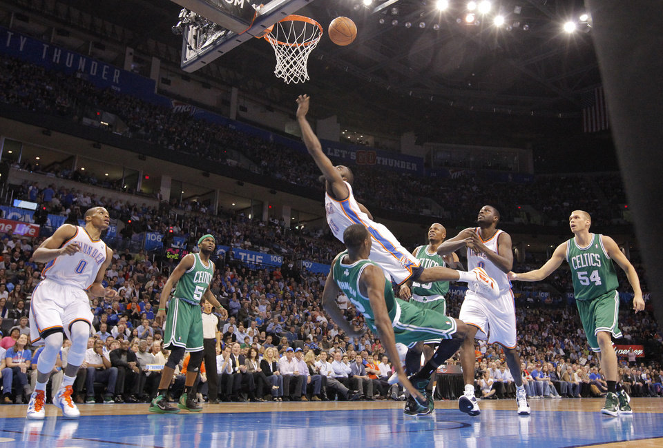 Photo - Oklahoma City Thunder guard James Harden (13) goes over the top of Boston Celtics forward JaJuan Johnson (12) during the NBA basketball game between the Oklahoma City Thunder and the Boston Celtics at the Chesapeake Energy Arena on Wednesday, Feb. 22, 2012 in Oklahoma City, Okla.  Photo by Chris Landsberger, The Oklahoman
