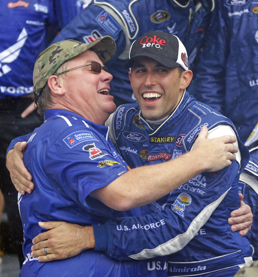 Photo - Aric Almirola, right, celebrates with crew member Jeff Keller, left, in Victory Lane after winning the NASCAR Sprint cup Series auto race at Daytona International Speedway in Daytona Beach, Fla., Sunday, July 6, 2014. (AP Photo/John Raoux)