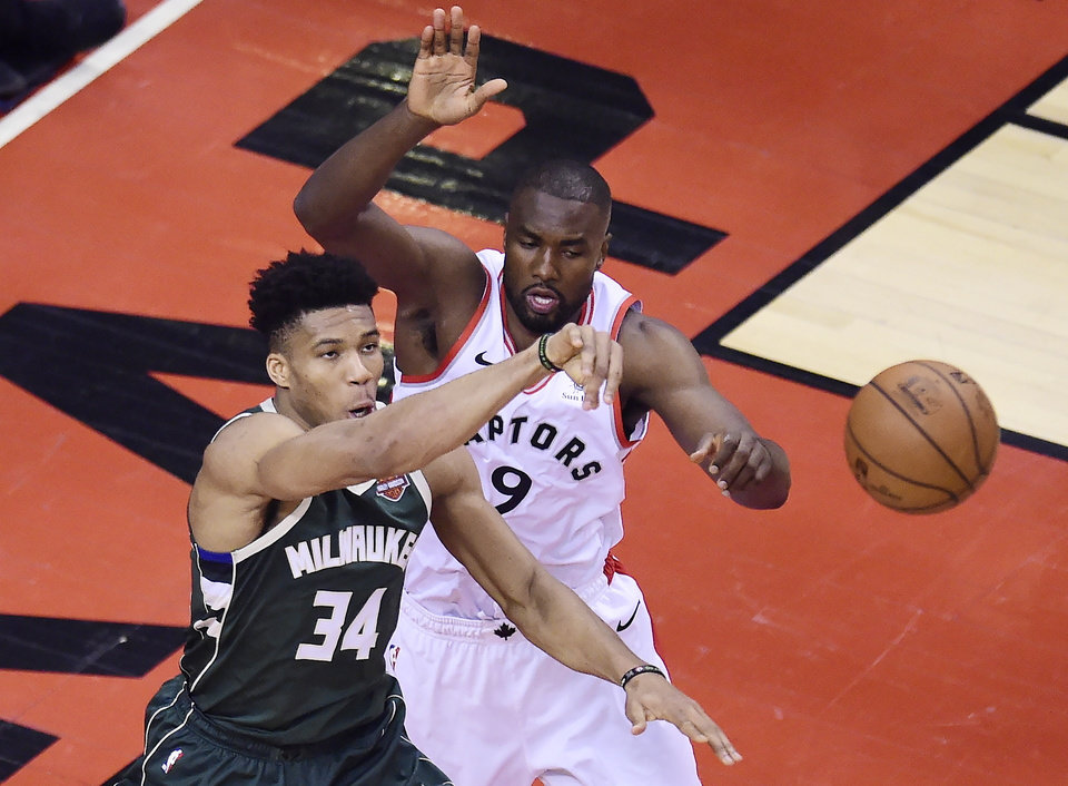 Photo - Milwaukee Bucks forward Giannis Antetokounmpo (34) passes off the ball as Toronto Raptors centre Serge Ibaka (9) defends during first half NBA Eastern Conference finals basketball action in Toronto on Sunday, May 19, 2019. (Nathan Denette/The Canadian Press via AP)