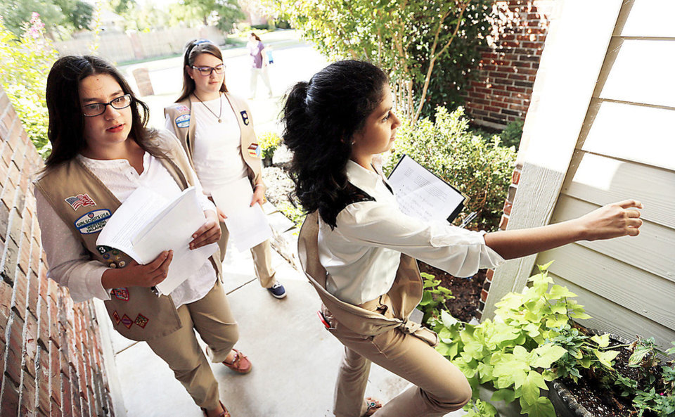 Photo - Melanie Michaud, Kaete-Marie Legler and Tanvi Saran, all 13, carry petitions door to door as they work on their Silver Award Girl Scout project on Friday in Norman.  Photo by Steve Sisney, The Oklahoman  STEVE SISNEY - THE OKLAHOMAN