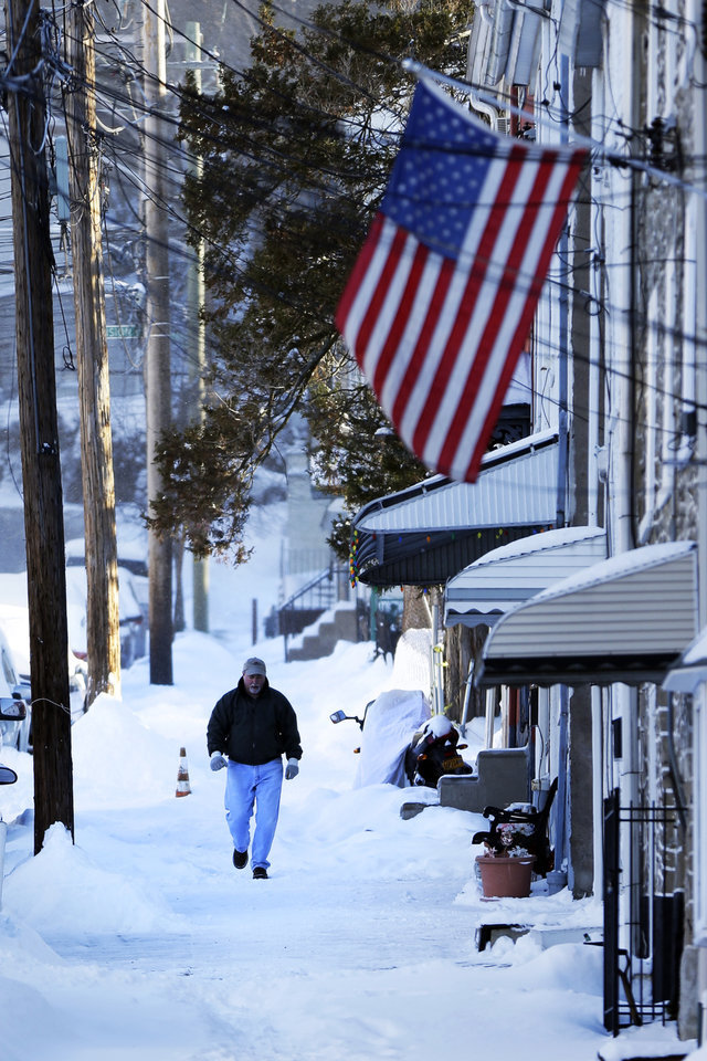 Photo - A man walks on an un-shoveled sidewalk in the aftermath of a snowstorm Wednesday, Jan. 22, 2014, in Philadelphia.  A winter storm stretched from Kentucky to New England and hit hardest along the heavily populated Interstate 95 corridor between Philadelphia and Boston.   (AP Photo/Matt Rourke)