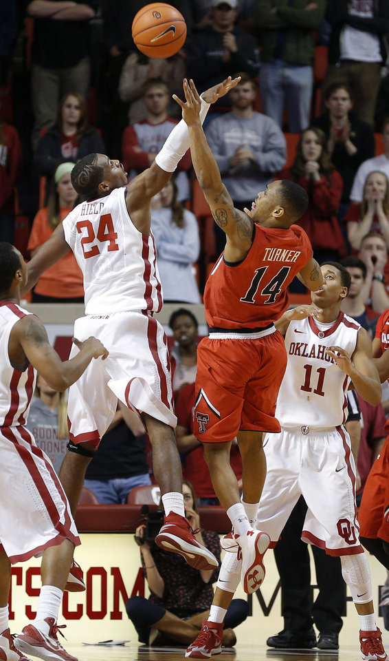 Photo - Texas Tech's Robert Turner (14) makes a basket from between Oklahoma's Buddy Hield (24) and Oklahoma's Isaiah Cousins (11) during an NCAA college basketball game between the University of Oklahoma and Texas Tech University at the Lloyd Noble Center in Norman, Okla., Wednesday, Feb. 12, 2014. Oklahoma lost 68-60. Photo by Bryan Terry, The Oklahoman