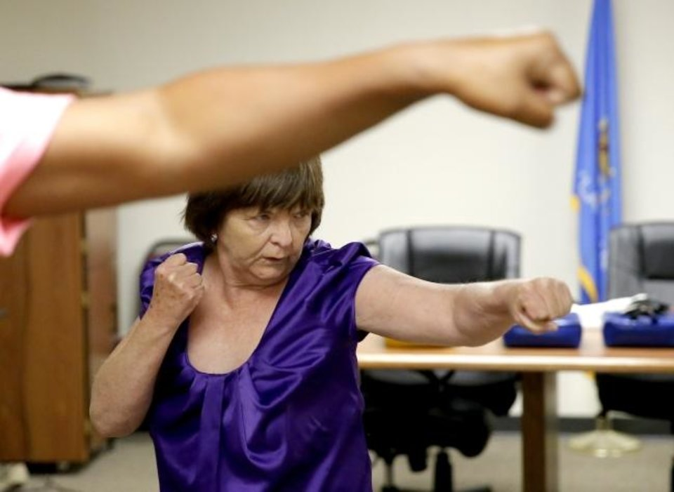 Photo - Sharon Strickland preforms moves in a self-defense class in Oklahoma City, Thursday, Aug. 8, 2019. [Sarah Phipps/The Oklahoman]
