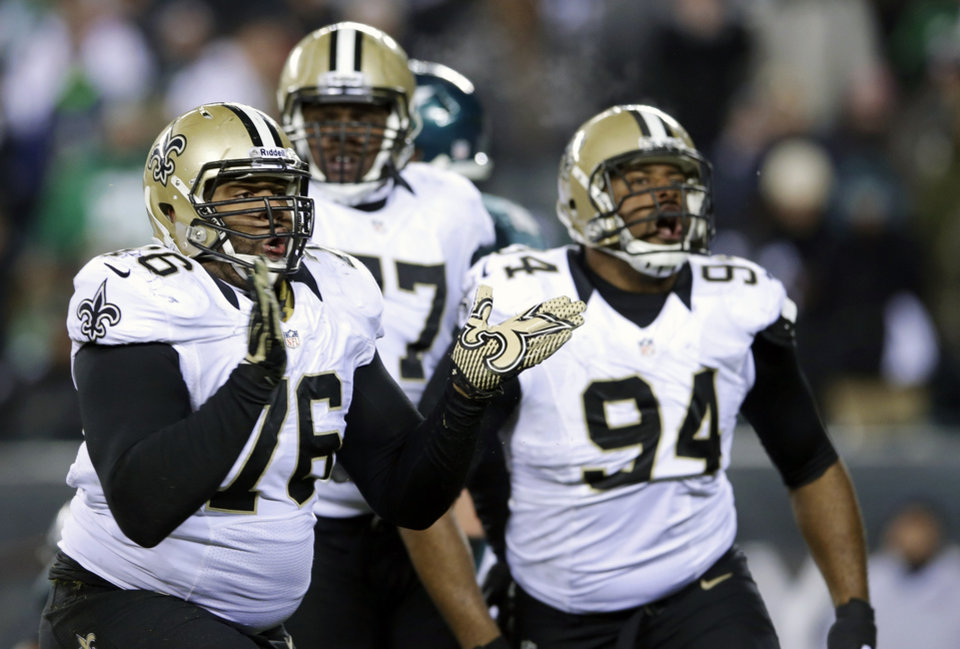 Photo - New Orleans Saints' Akiem Hicks (76) and Cameron Jordan (94) celebrate after tackling Philadelphia Eagles' Nick Foles during the second half of an NFL wild-card playoff football game, Saturday, Jan. 4, 2014, in Philadelphia. (AP Photo/Michael Perez)