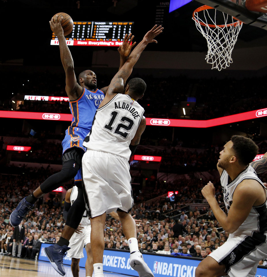 Photo - Oklahoma City's Serge Ibaka (9) shoots over San Antonio's LaMarcus Aldridge (12) during Game 2 of the second-round series between the Oklahoma City Thunder and the San Antonio Spurs in the NBA playoffs at the AT&T Center in San Antonio, Monday, May 2, 2016. Photo by Bryan Terry, The Oklahoman