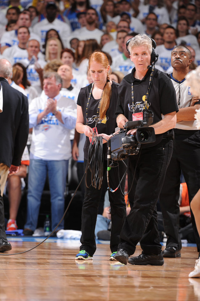 Photo - Army Reserve Spec. Elizabeth Fowler of Oklahoma City helps an NBA Entertainment cameraman during the Finals game at the Chesapeake Arena last week. PHOTO BY ANDREW D. BERNSTEIN / NBAE  Andrew D. Bernstein