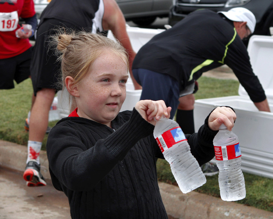 Photo - Berkley Owens, 8, a student at Soldier Creek Elementary School, was one of several Midwest City YMCA volunteers giving bottled water to runners at the finish line. Owens ' dad participated in the run.  The Renaissance Run, a  5K run and walk begins at 8:30 a.m. at the Midwest City Community Center. Following the race, runners are invited to enjoy a pancake breakfast  at Midwest Regional Medical Center, 2825 Parklawn Drive on Saturday, Sep. 15, 2012,  Photo by Jim Beckel, The Oklahoman.