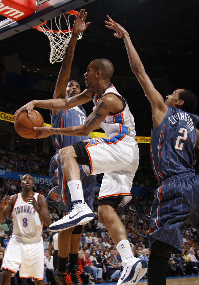 Photo - Oklahoma City's Eric Maynor (6) goes between Charlotte's Tyrus Thomas (12) and Shaun Livingston (2) during an NBA basketball game between the Oklahoma City Thunder and the Charlotte Bobcats at the Oklahoma City Arena, Friday, March 18, 2011. Photo by Bryan Terry, The Oklahoman