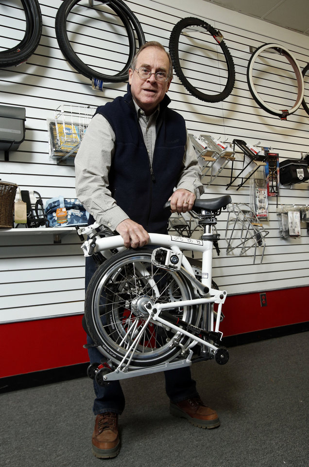 Photo - Hank Ryan, co-owner of Al's Bicycles, holds a folded Brompton bicycle. Photo by STEVE SISNEY, THE OKLAHOMAN