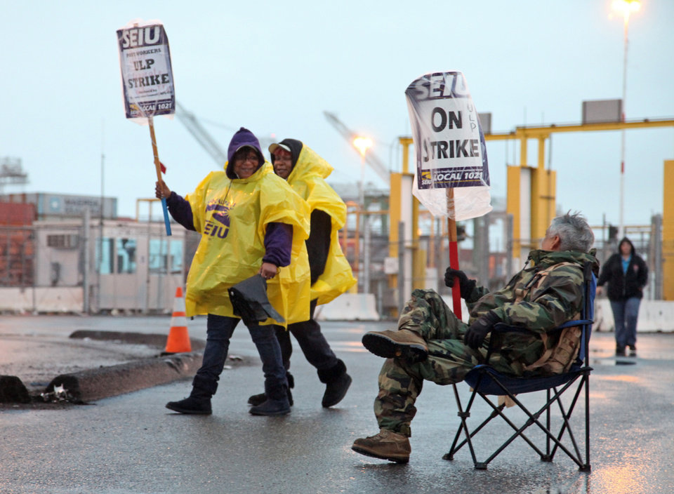 Port workers represented by SEIU Local 1021 take part in a 24-hour strike at the Port of Oakland in Oakland, Calif., in the early morning hours on Tuesday, Nov. 20, 2012 (AP Photo/The Tribune,Laura Oda )
