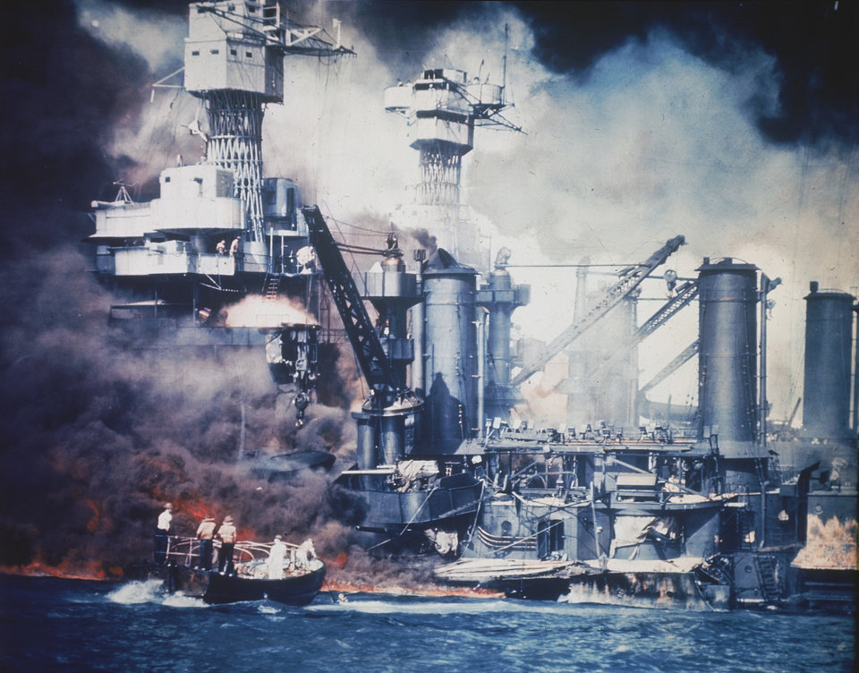 FILE - In this U.S. Navy file photo, a small boat rescues a USS West Virginia crew member from the water after the Japanese bombing of Pearl Harbor, Hawaii on Dec. 7, 1941 during World War II. Two men can be seen on the superstructure, upper center. The mast of the USS Tennessee is beyond the burning West Virginia. On Dec. 7, 1941, Japanese Imperial Navy navigator Takeshi Maeda guided his Kate bomber to Pearl Harbor and fired a torpedo that helped sink the USS West Virginia. President Barack Obama on Thursday Dec. 6, 2012 issued a proclamation declaring Dec. 7 a day of remembrance in honor of the 2,400 Americans who died at Pearl Harbor. He urged federal agencies, organizations and others to fly their flags at half-staff. (AP Photo, File)