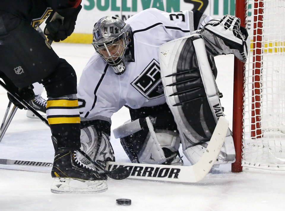 Photo - Los Angeles Kings goalie Jonathan Quick (32) keeps his eyes on the puck while protecting the net during the second period of an NHL hockey game against the Boston Bruins in Boston Monday, Jan. 20, 2014. (AP Photo/Elise Amendola)
