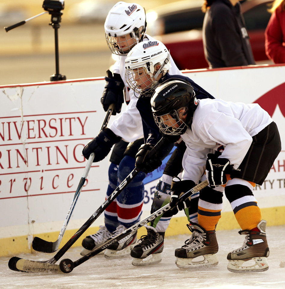 Players reach for the puck in an ice hockey game Saturday at the Norman Outdoor Holiday Ice Rink.
