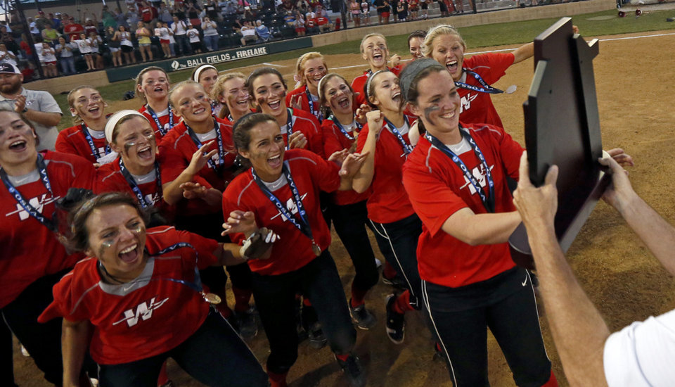 Photo -                    Washington players race to hoist the state championship trophy after beating Dale for the Class 4A state slowpitch softball championship in Shawnee on Tuesday.                     Photo by Bryan Terry, The Oklahoman
