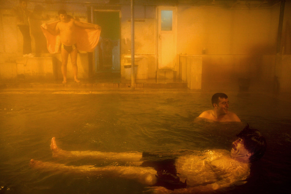Photo - In this Feb. 19, 2014 photo, Iranian men relax at a hot mineral pool, in the northwestern town of Sarein, Iran. The steamy waters emanating from the depths of the earth are rich in sulfur, calcium, lithium and other minerals, and are believed to offer relief to patients suffering from joint pain and some skin diseases. (AP Photo/Ebrahim Noroozi)