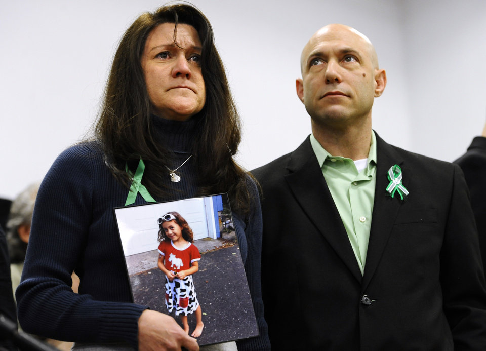 Photo - Jennifer Hensel, holding a portrait of her daughter, Sandy Hook School shooting victim Avielle Rose Richman, stands with her husband Jeremy Richman at a news conference at Edmond Town Hall in Newtown, Conn., Monday, Jan. 14, 2013. One month after the mass school shooting at Sandy Hook Elementary School, the parents joined a grassroots initiative called Sandy Hook Promise to support solutions for a safer community. (AP Photo/Jessica Hill)