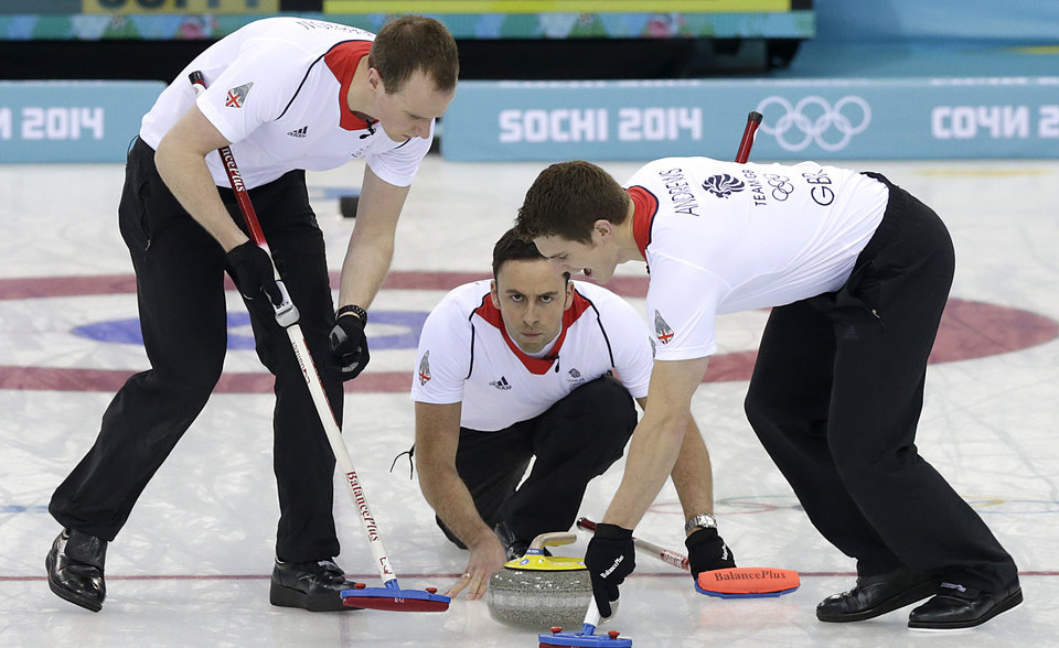 Photo - Britain's skip David Murdoch, center, delivers the rock while Michael Goodfellow, left, and Scott Andrews, sweep the ice during the men's curling gold medal game against Canada at the 2014 Winter Olympics Friday, Feb. 21, 2014, in Sochi, Russia. (AP Photo/Wong Maye-E)