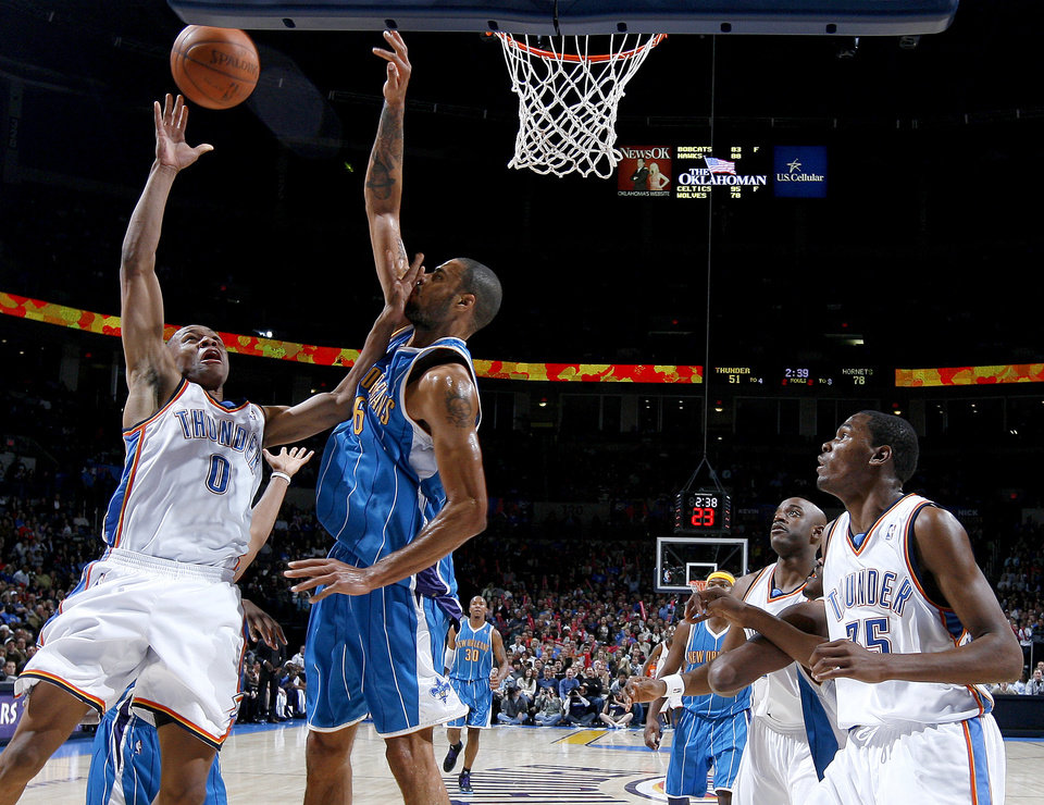 Photo - Oklahoma City's Russell Westbrook shoots over Tyson Chandler of New Orleans as Kevin Durant watches during the NBA basketball game between the Oklahoma City Thunder and the New Orleans Hornets at the Ford Center in Oklahoma City on Friday, Nov. 21, 2008.   BY BRYAN TERRY, THE OKLAHOMAN