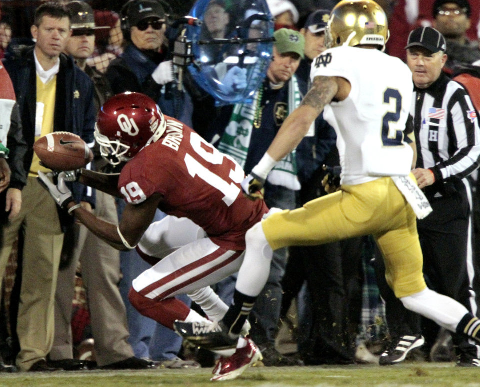 Photo - Oklahoma wide receiver Justin Brown (19) makes a catch in front of Notre Dame cornerback Bennett Jackson (2) during the first half of the college football game between the University of Oklahoma Sooners (OU) and the Fighting Irish of Notre Dame (ND) at Gaylord Family-Oklahoma Memorial Stadium in Norman, Okla., on Saturday, Oct. 27, 2012. Photo by Steve Sisney, The Oklahoman