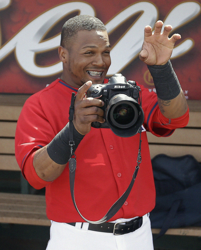 Photo - Los Angeles Angels's Erick Aybar has fun with a camera before an exhibition spring training baseball game against the Chicago White Sox, Thursday, March 13, 2014, in Tempe, Ariz. (AP Photo/Morry Gash)