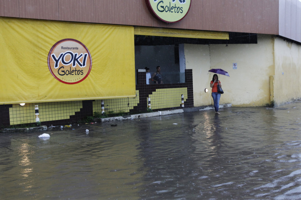 Photo - A woman waits on the sidewalk on a flooded street after heavy rain storms in Recife, Brazil, Thursday, June 26, 2014. The World Cup soccer match between the USA and Germany will be played at the Arena Pernambuco in Recife today.  (AP Photo/Petr David Josek)