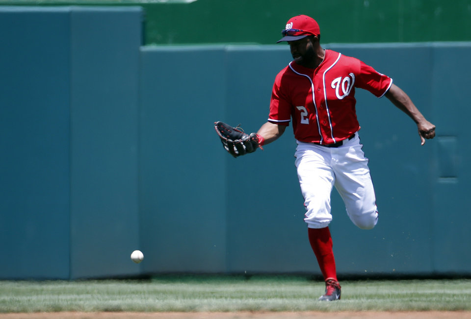 Photo - Washington Nationals center fielder Denard Span (2) cannot catch a fly ball hit by Texas Rangers' Alex Rios, and is charged with an error, during the first inning of a baseball game at Nationals Park, Sunday, June 1, 2014, in Washington. (AP Photo/Alex Brandon)